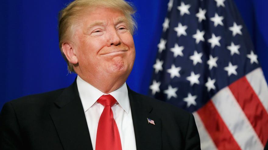 El presidente Donald Trump sonríe ante la bandera de Estados Unidos