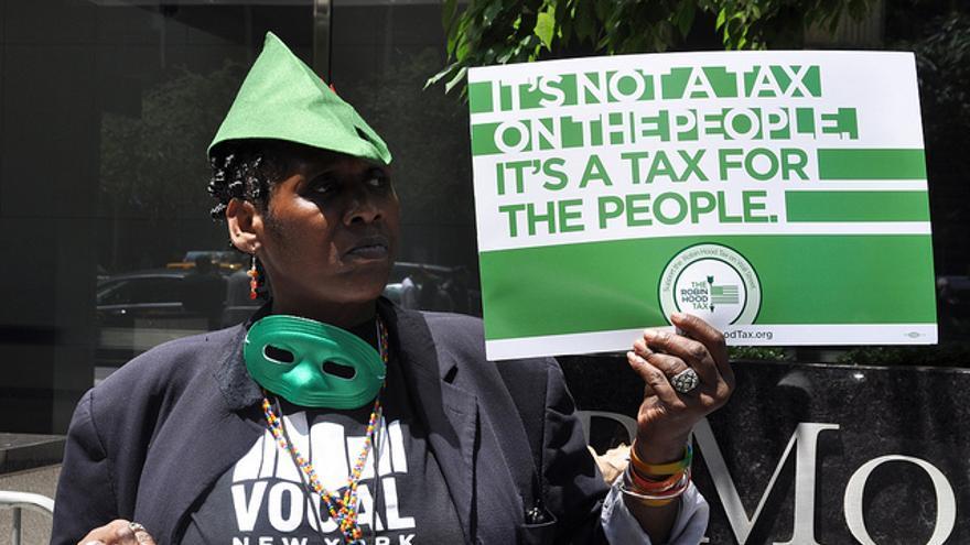 Manifestante en favor de la Tasa Tobin frente a la sede de JP Morgan en Nueva York en junio de 2012. Flickr de Michael Fleshman CC.