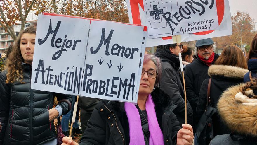 """Una mujer alza un cartel con la consigna """"mejor atención, menor problema"""", este domingo en Hortaleza"""