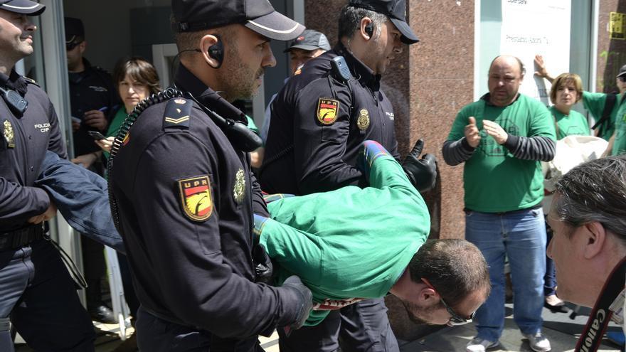 La policía saca en volandas al denunciado, Óscar Manteca.   RUBÉN VIVAR