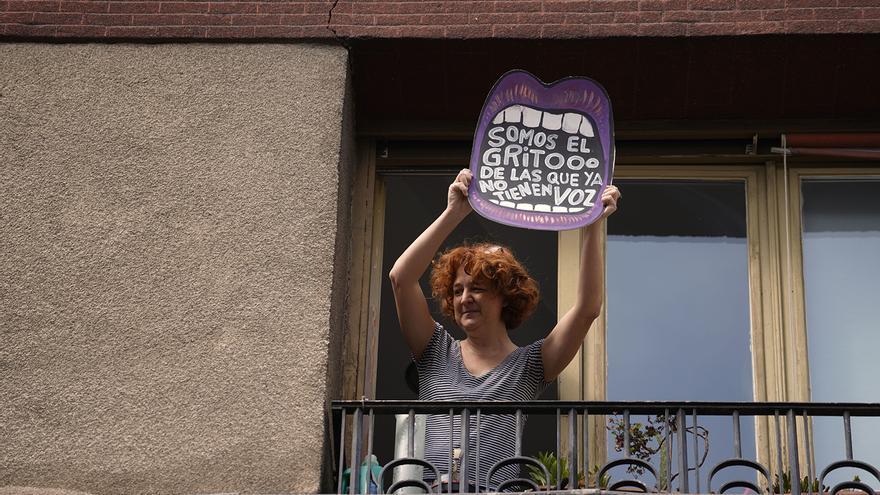 """Una mujer, desde un balcón de Madrid el pasado 8M, con una pancarta que reza: """"Somos el grito de las que ya no tienen voz""""."""