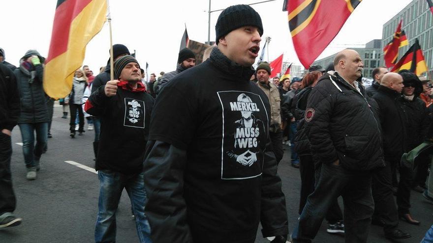 """Manifestante perteneciente al grupo de los """"rusos alemanes"""" con una camiseta con la inscripción """"Merkel tiene que irse"""" durante la manifestación"""