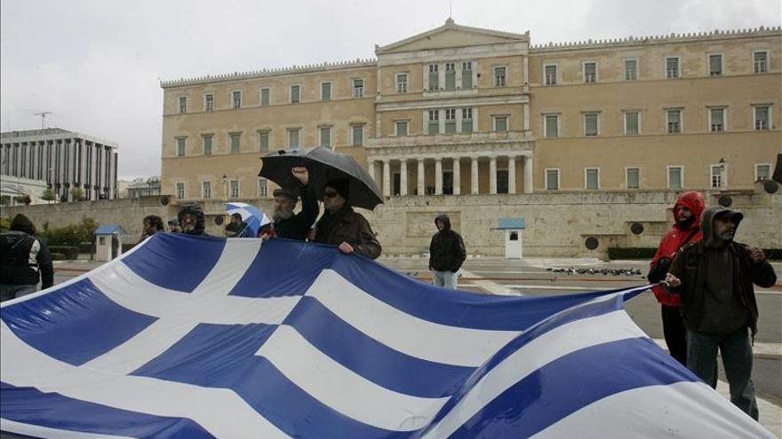 Manifestantes despliegan una bandera de Grecia frente al Parlamento en Atenas.