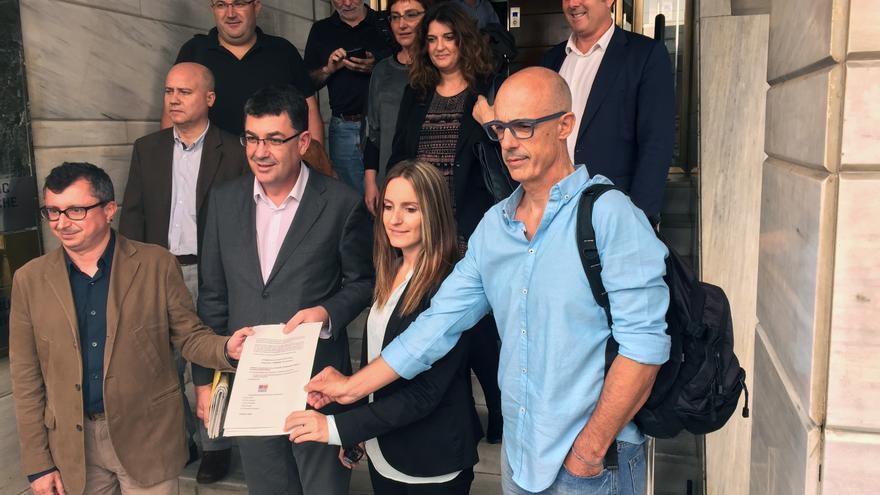 Representantes de Compromís y Podemos muestran el documento que han firmado ante notario