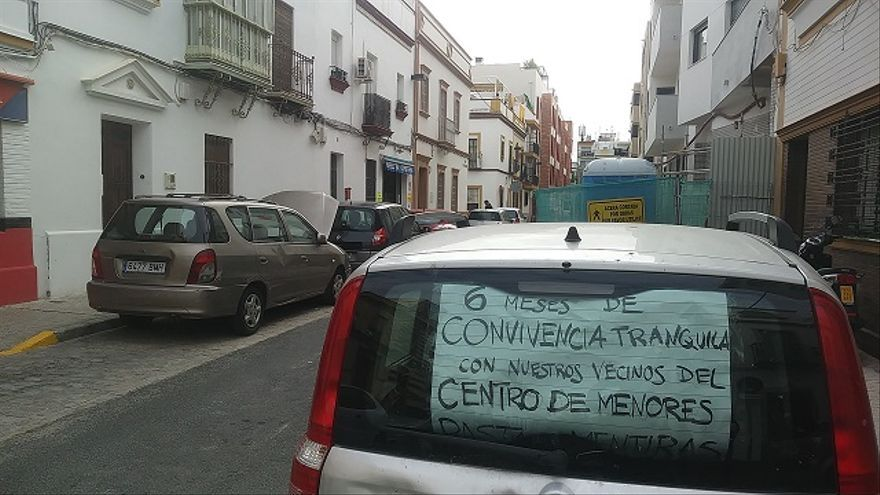 Cartel en el interior de un coche a unos metros de la convocatoria de Vox en Sevilla