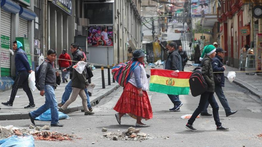 Ciudadanos bolivianos caminan por una de las calles céntricas donde los ingresos a Plaza Murillo están bloqueados, este lunes en La Paz (Bolivia)