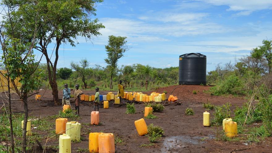 Refugiados se reúnen para recoger el agua en uno de los tanques de agua en el asentamiento de refugiados de Palorinya.