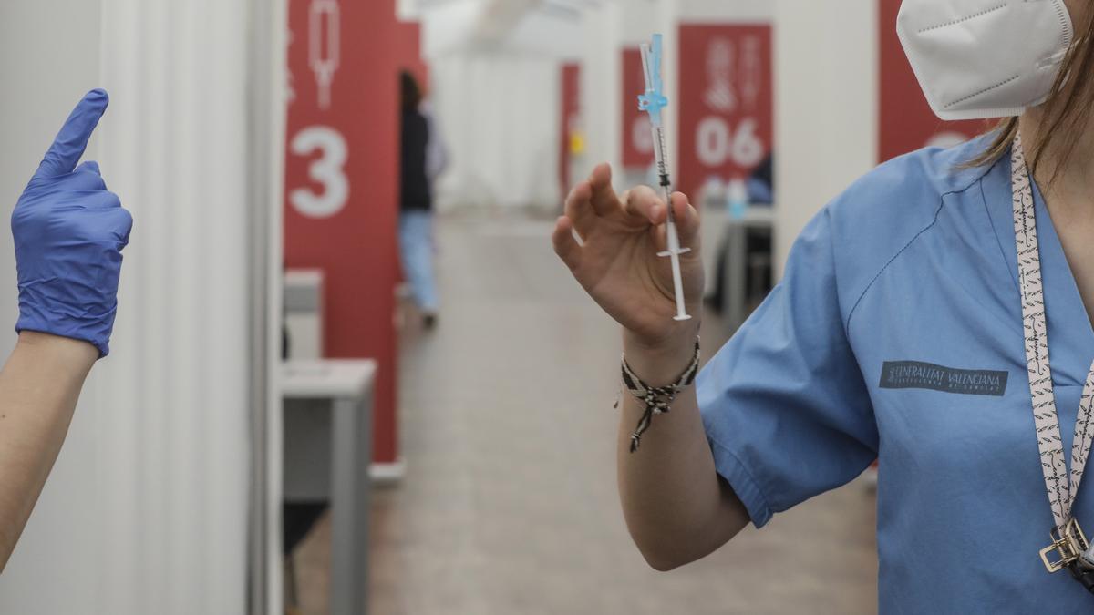 Una profesional sanitaria sostiene una jeringuilla con la vacuna de AstraZeneca, en el Hospital la Fe, en Valencia