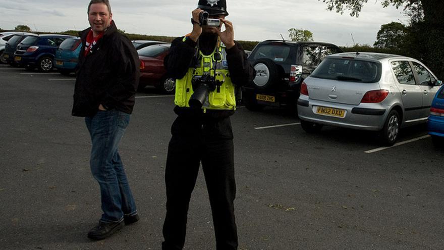 Un policía británico saca una foto mientras un transeúnte mira