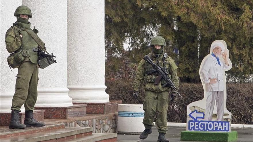 Dos hombres con uniformes militares y armas de fuego vigilan la entrada del aeropuerto de Simferópol en Crimea. Foto: Efe.