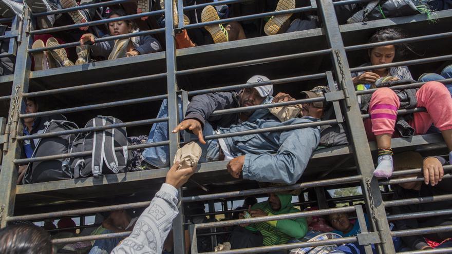 Los migrantes centroamericanos, parte de la caravana que espera llegar a la frontera con Estados Unidos, reciben alimentos donados mientras viajan en un camión, en Celaya, México, el domingo 11 de noviembre de 2018. Foto: AP/Rodrigo Abd