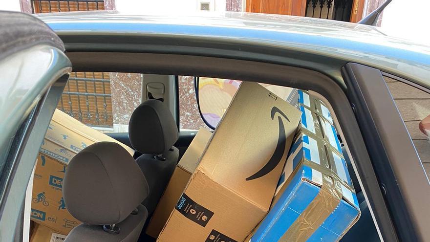 Carteros rurales con paquetes de Amazon en el coche