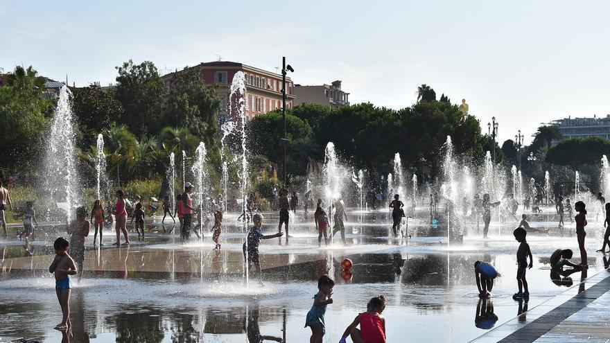 Varios niños y adultos combaten las altas temperaturas refrescándose en una fuente pública