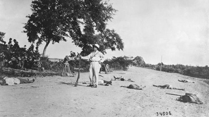 Un norteamericano posa junto a los cadáveres de insurgentes haitianos muertos en un enfrentamiento con marines en 1915.