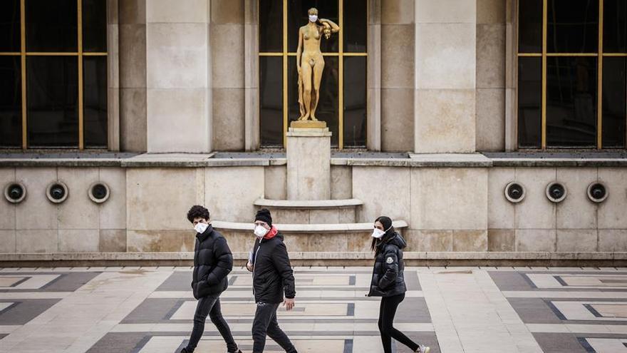Tres jóvenes pasean con mascarilla por el centro de París, Francia.
