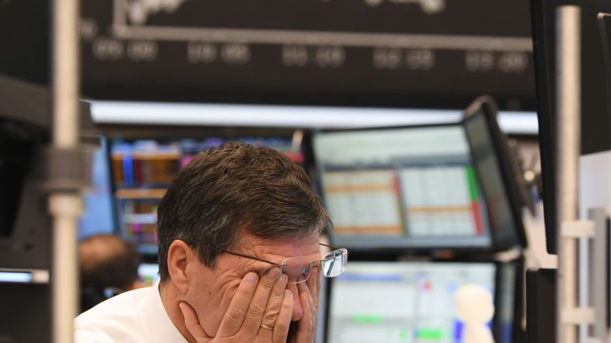 09 March 2020, Hessen, Frankfurt/Main: A stock trader rubs his eyes on the floor of the Frankfurt Stock Exchange. Stock exchanges around the world are reacting with huge losses to the fall in oil prices and concerns about the economic consequences of the