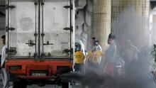 Un chorro de humo negro emana del tubo de escape de un camión de reparto.