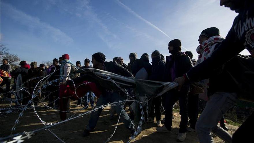 Un grupo de refugiados trataba el miércoles de saltar la valla que separa Macedonia de Grecia, en la localidad fronteriza de Idomeni.