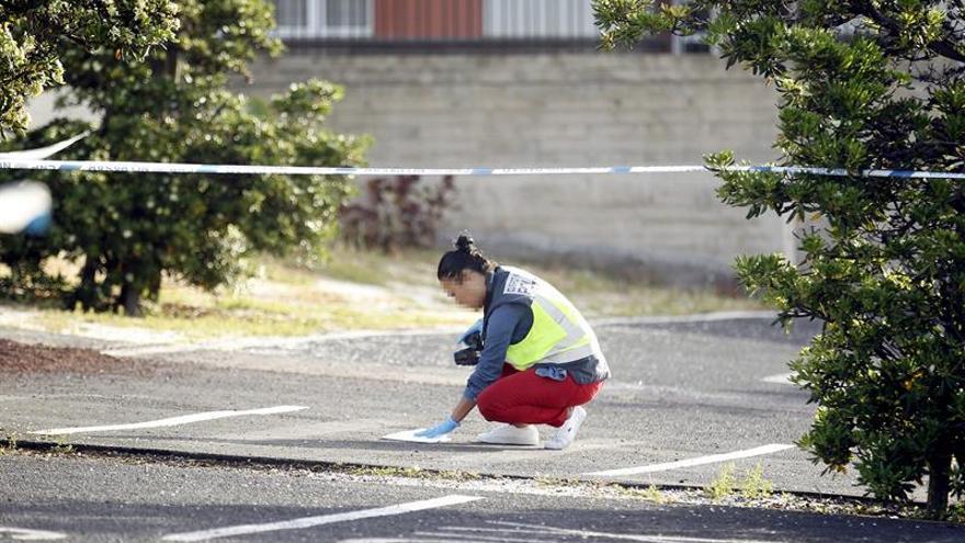 Una policía recoge muestras del lugar donde dispararon a Carlos Machín