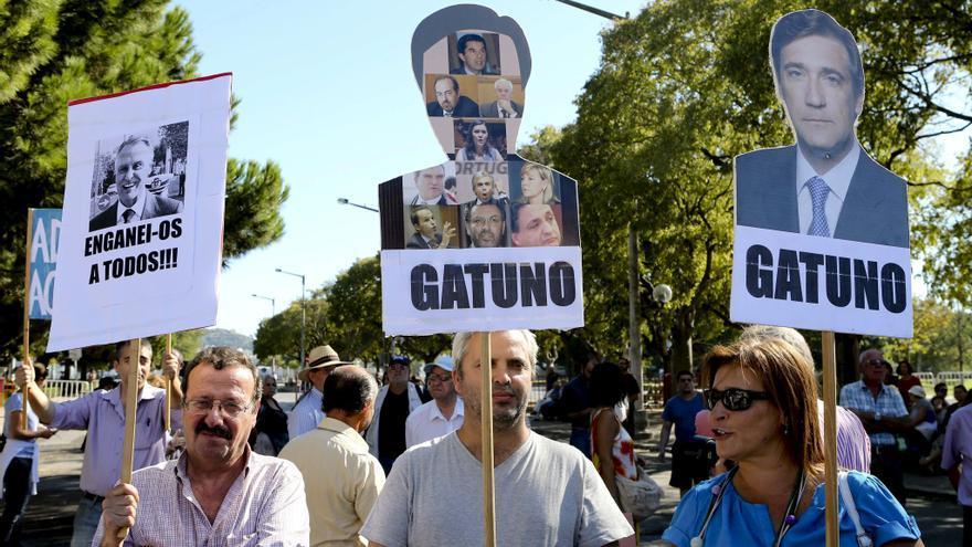 """Unos manifestantes sostienen pancartas con el retrato de Passos Coelho, en las que se lee la palabra """"ladrón"""" en Lisboa, el 21 de septiembre. Foto: EFE"""