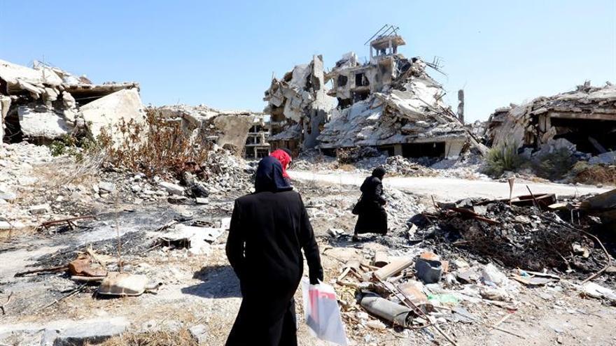 Mujeres sirias caminan entre las ruinas de la ciudad Homs, Siria.