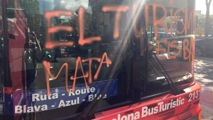 """Imatge del bus turístic amb la pintada """"El turisme mata els barris"""""""