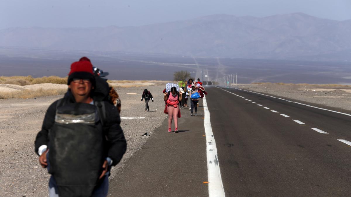 Migrantes de Venezuela caminan sobre el arcén de una carretera después de cruzar a Chile desde la frontera con Bolivia, cerca de Colchane, Chile, el sábado 2 de febrero.
