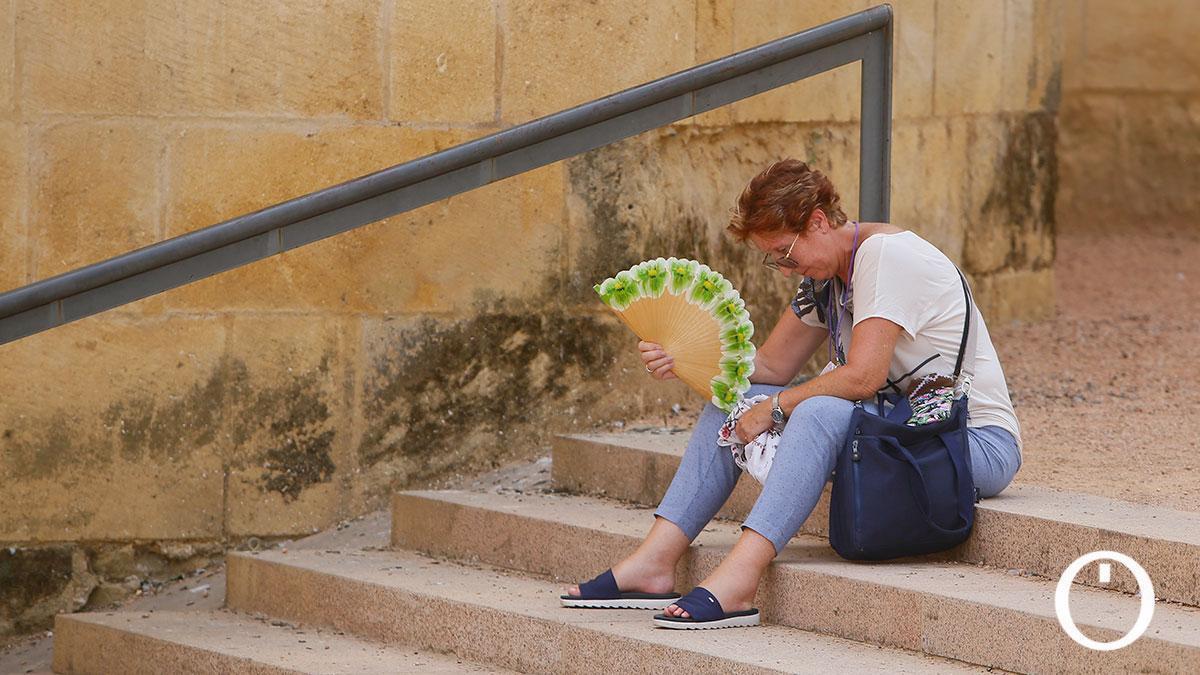 Una mujer se abanica cerca del Puente Romano