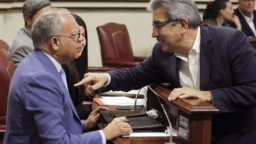 Los diputados Casimiro Curbelo (i) y Román Rodríguez conversan en el Parlamento de Canarias