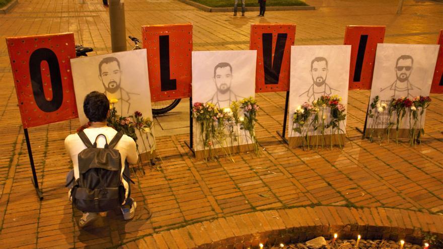 Un chico coloca flores ante la imagen de uno de los asesinados en una vigilia celebrada el lunes en Bogotá.