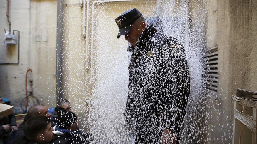 Un policía nacional cubierto por bolitas de poliespán lanzadas por los activistas antidesahucios cuando los agentes entraron al patio delantero de la vivienda.