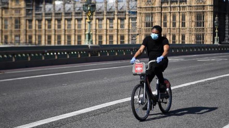Una persona montando en bicicleta con mascarilla en Londres.