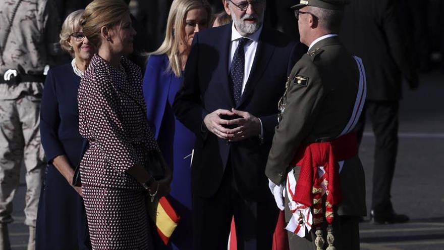El presidente del Gobierno, Mariano Rajoy (c), conversa con la ministra de Defensa, María Dolores de Cospedal (i), y el Jefe del Estado Mayor de la Defensa (Jemad), el general Fernando Alejandre Martínez, momentos antes del comienzo del desfile del Día de la Fiesta Nacional, al que asiste el Gobierno en pleno y la mayoría de líderes políticos.