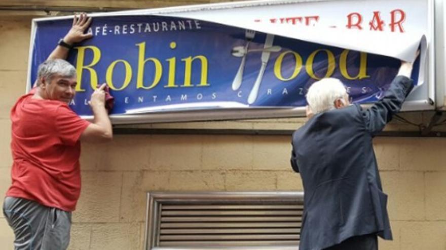 El Padre Ángel, colocando el cartel del primer Robin Food   MENSAJEROS DE LA PAZ