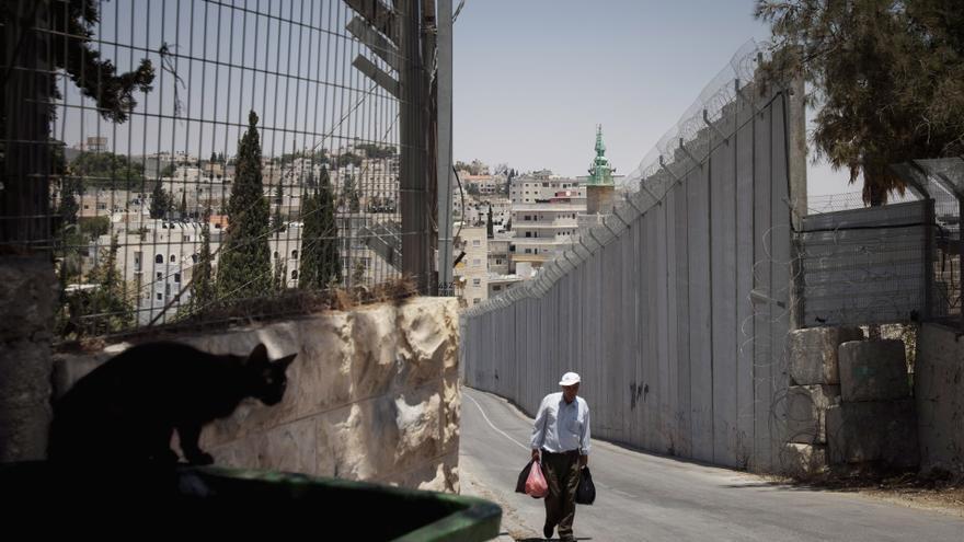 Un hombre palestino camina junto al muro separación de Israel en Abu Dis, en las afueras de Jerusalén.