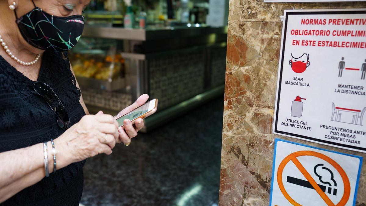 Una mujer busca en su móvil su certificado Covid momentos antes de acceder al interior de una cafetería de Santa Cruz de Tenerife.