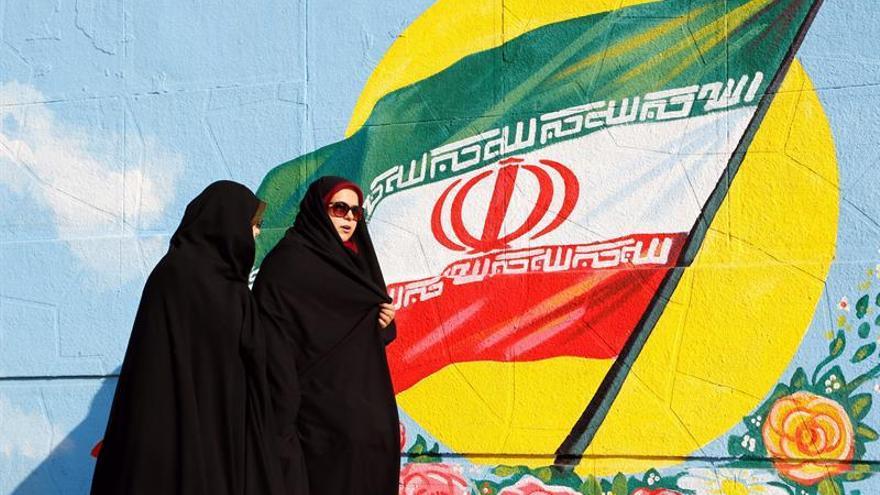 Dos mujeres iraníes pasan sobre un mural con la bandera nacional.