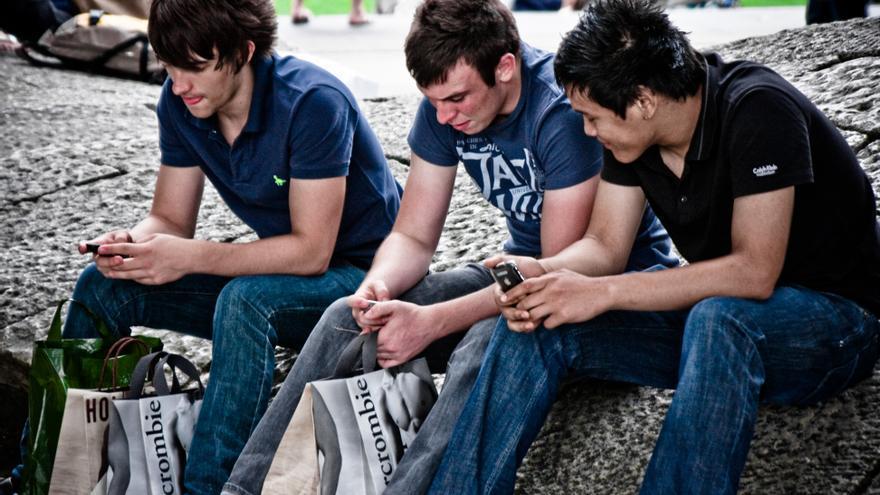Tres chicos mirandos sus teléfonos móviles. | Foto: cc Garry Knight. Licencia: https://creativecommons.org/licenses/by/2.0/