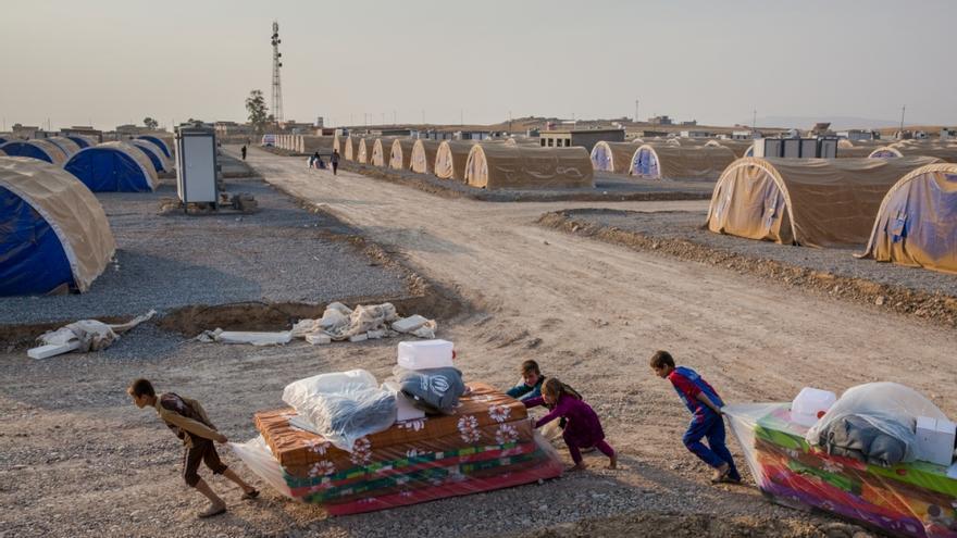 Niños iraquíes desplazados transportan colchones y otros útiles en el campamento de Hasansham, en octubre pasado.