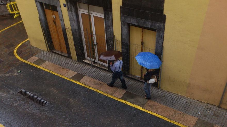 Dos viandantes se protegen de la lluvia, en la ciudad de Santa Cruz