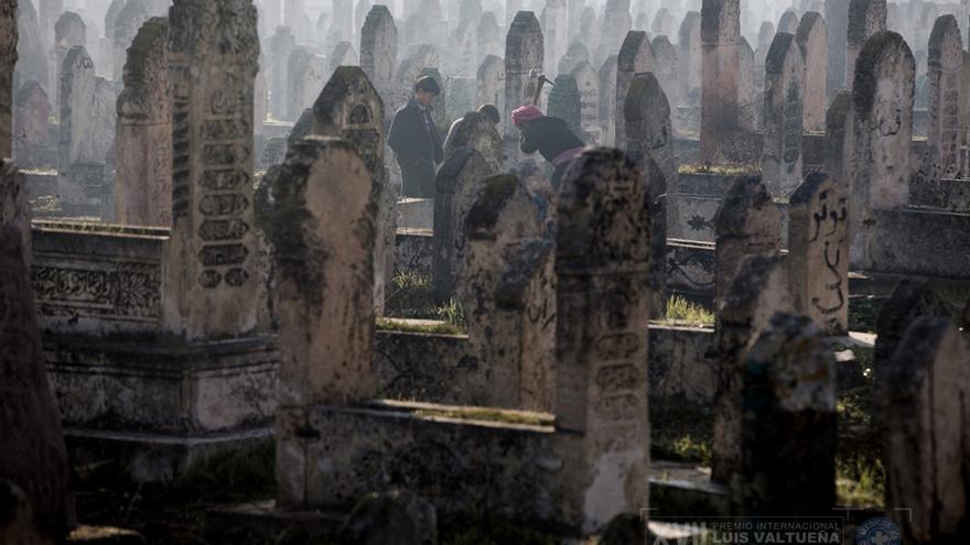 Un hombre está cavando una tumba en un cementerio en Alepo, mientras que los niños miran./ Niclas Hammarström
