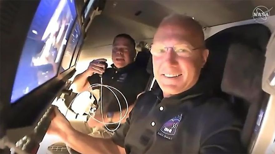 A handout video-grabbed still image made available by NASA on 31 May 2020 shows NASA astronauts Doug Hurley (foreground) and Bob Behnken call down to mission controllers for a report on their second flight day onboard the SpaceX Crew Dragon spacecraft on NASA's SpaceX Demo-2 mission approaching to dock to the International Space Station (ISS), 31 May 2020.