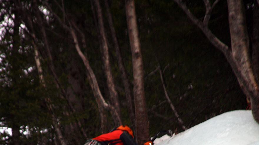 Un escalador saliendo de una vía de escalada en hielo. Esta es la zona de mayor peligro si no se está atento y no se tiene la cuerda colocada de manera correcta para no tropezar y caer boca abajo. El escalador está colocado correctamente, pero conviene colocar un seguro cerca de la salida.