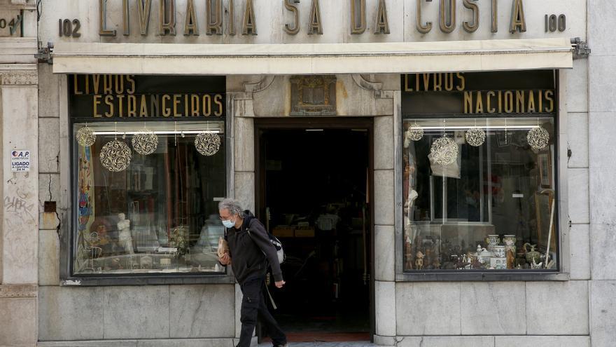 Hombre con mascarilla frente a un comercio en Lisboa (Portugal)