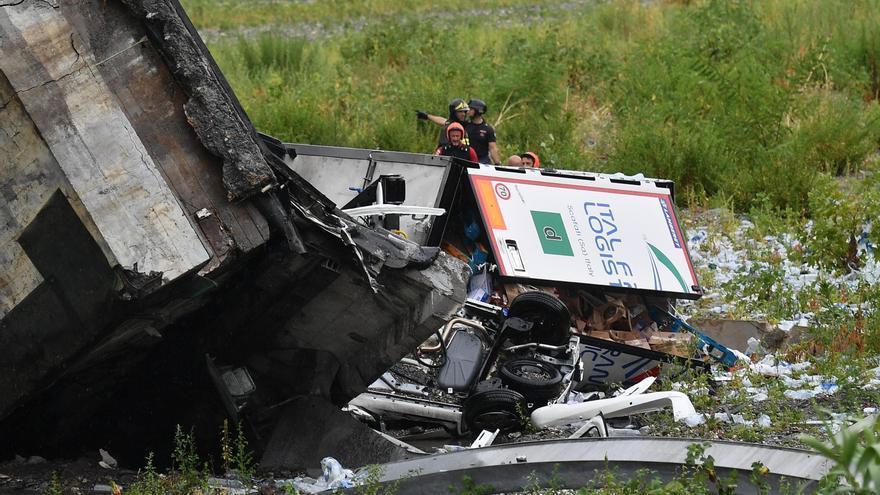 Miembros de los servicios de emergencia buscan entre los escombros tras derrumbarse una sección del viaducto Morandi en Génova (Italia)