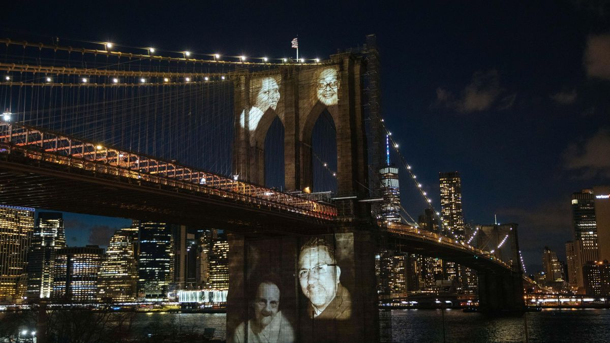 """Imágenes de personas que murieron por complicaciones relacionadas con la COVID-19 fueron proyectadas este domingo sobre el Puente de Brooklyn, durante una ceremonia conmemorativa para recordar a las más de 30.000 víctimas de la pandemia en la """"gran manzana"""", en el distrito de Brooklyn (NY, EE.UU.)."""