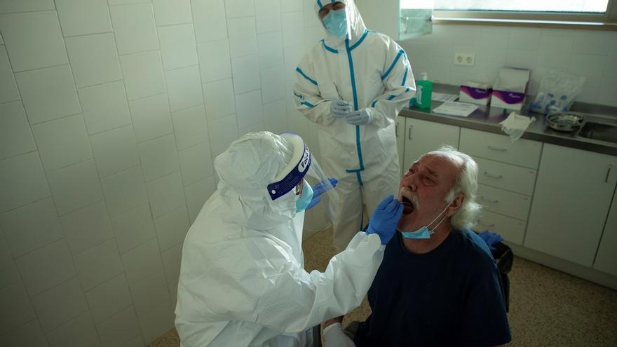 Toma de una muestra en la garganta de un hombre para realizar un test de COVID–19