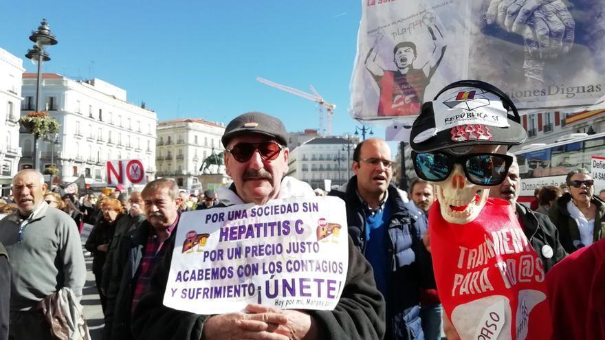 Varios manifestantes portan pancartas y una calavera exigiendo tratamiento para la Hepatitis C.