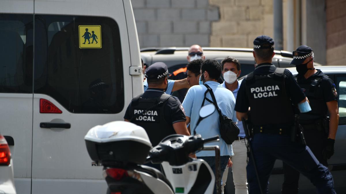 Varios agentes y vehículos de la Policía Local de Ceuta acompañan a menores no acompañados hacia una furgoneta, en las inmediaciones del Polideportivo Santa Amelia.