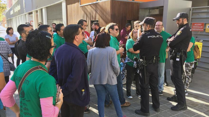 Dos agentes de la Policía Nacional dialogan con los miembros de la PAH concentrados a las puertas del edificio donde iba a producirse el desahucio